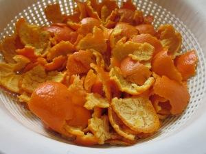 A banda, escaldem en aigua bullent les pells de mandarina durant cinc minuts, colem i tallem finament.